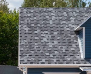 The roof of the house lined with gray bitumen shingles