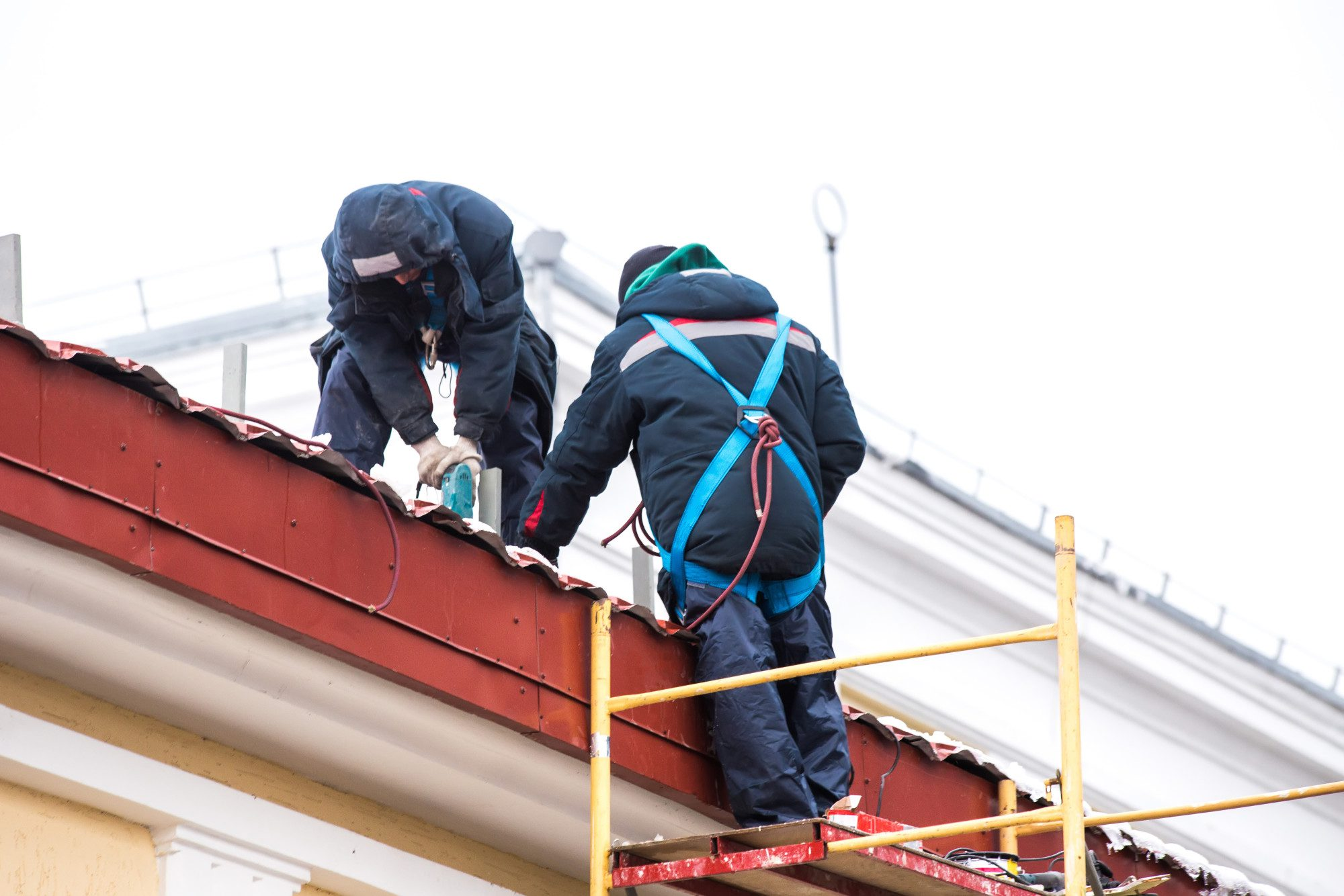 Two high-altitude workers work on the roof with insurance