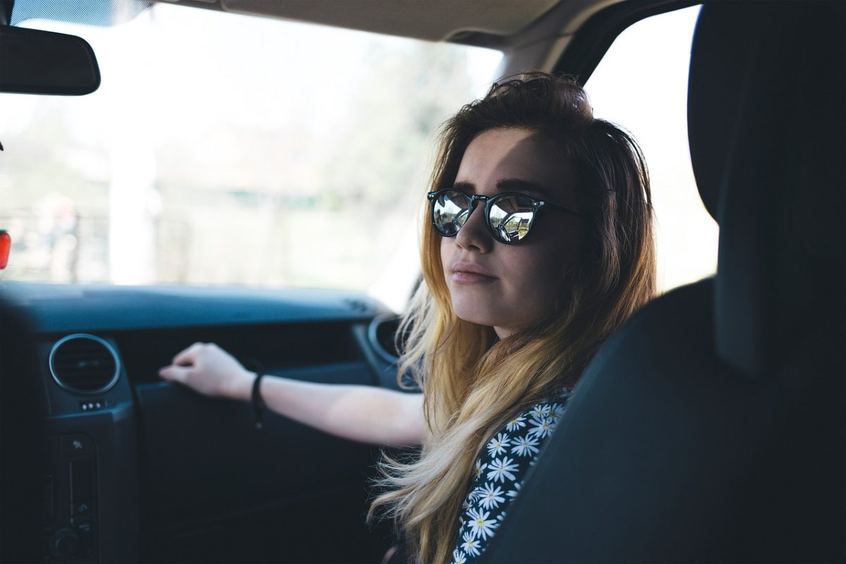 women sitting in the passenger seat with sunglasses